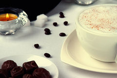 Coffee cup,coffee beans, chocolate candies and candle Stock Photography