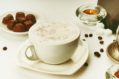 Coffee cup, coffee beans, chocolate candies and candle Stock Photo