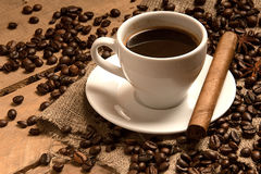 Coffee cup with coffee beans, cigar on bagging and wood. Royalty Free Stock Images