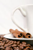 Coffee cup with coffee beans and cinnamon. Royalty Free Stock Images