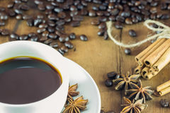 A coffee on the cup with coffee beans and cinnamon sticks on wood Royalty Free Stock Photo