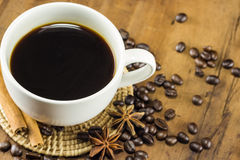 A coffee on the cup with coffee beans and cinnamon sticks on wood Royalty Free Stock Photos
