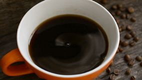 Coffee cup and coffee beans. On the olf wooden table close up slow motion footage stock video