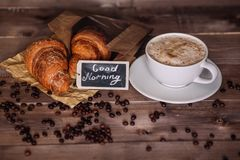 Coffee cup and coffee beans , croissant on brown wooden table Royalty Free Stock Photos