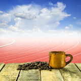 Coffee cup and coffee beans at curve of a running track Royalty Free Stock Photography