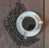 Coffee cup and coffee beans on old wooden desk background.  Royalty Free Stock Photo