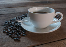 Coffee cup and coffee beans on old wooden table background.  Royalty Free Stock Images