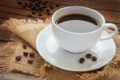 Coffee cup and coffee beans on sackcloth Stock Photo