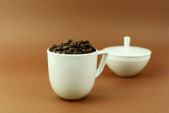 Coffee cup with coffee beans and with sugar bowl.  Royalty Free Stock Photography