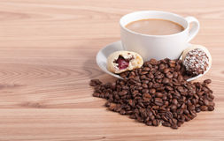 Coffee cup and coffee beans, sweets on the wooden background Stock Image