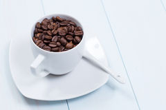 Coffee cup with coffee beans on table. Coffee cup full of coffee beans on a wood table Stock Photos
