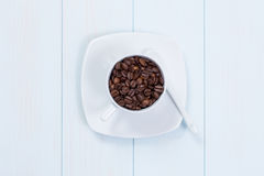 Coffee cup with coffee beans on table. Coffee cup full of coffee beans on a wood table Royalty Free Stock Image