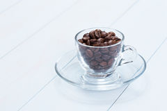 Coffee cup with coffee beans on table. Coffee cup full of coffee beans on a wood table Stock Images