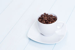 Coffee cup with coffee beans on table. Coffee cup full of coffee beans on a wood table Stock Image