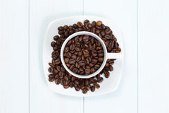 Coffee cup with coffee beans on table. Coffee cup full of coffee beans on a wood table Royalty Free Stock Photos
