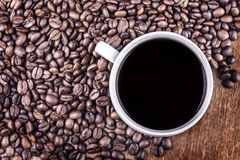 Coffee cup and coffee beans on table top view stock images