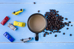 Coffee cup with coffee beans and toys car on the blue wooden bac Stock Image