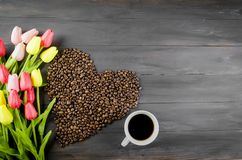 Coffee cup , Coffee beans and tulips. Coffee cup and scattered in the form of a heart of coffee grains on dark wooden background. bouquet of tulips and coffee Royalty Free Stock Photo