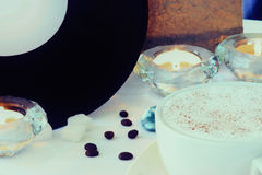 Coffee cup, coffee beans, vinyl plate and candles on a white table Royalty Free Stock Image