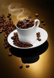 Coffee Cup with Coffee Beans. White coffee cup filled with coffee beans on gold background Stock Image