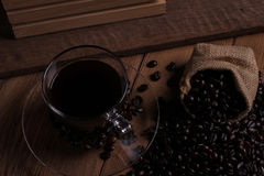 Coffee cup and coffee beans on wood background. Stock Photos