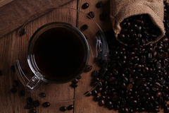 Coffee cup and coffee beans on wood background. Royalty Free Stock Photography