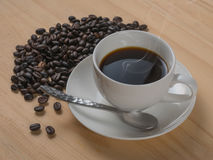 Coffee cup and coffee beans on wood table background.  Royalty Free Stock Photos