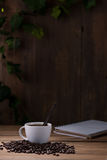 Coffee cup and coffee beans on wooden Royalty Free Stock Photos