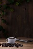 Coffee cup and coffee beans on wooden Stock Photography