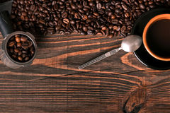 Coffee cup and coffee beans on wooden background. Top view. Stock Photos