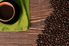 Coffee cup and coffee beans on wooden background. Top view. Royalty Free Stock Photo