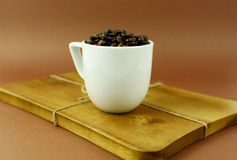 Coffee cup with coffee beans on wooden cutting board.  Stock Image