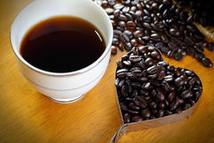 Coffee cup and coffee beans. On a wooden table Stock Images