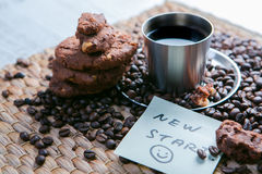 Coffee cup and coffee beans on wooden table with cookies and notepad with message on the sticker.  Royalty Free Stock Photos