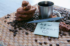 Coffee cup and coffee beans on wooden table with cookies and notepad with message on the sticker Stock Images
