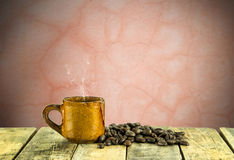 Coffee cup and coffee beans on wooden table with grunge backgrou Royalty Free Stock Photography