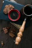 The coffee Cup and coffee maker and cookies are on stack of books stock images