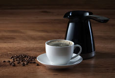 Coffee cup, coffee pot and beans on wooden texture Royalty Free Stock Photography