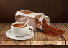 Coffee cup and coffee poured from a jar. Coffee cup dry coffee poured from a jar in the background Stock Photo