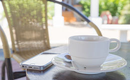 Coffee cup in coffee shop and Phone Royalty Free Stock Image