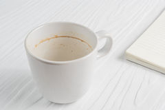 Coffee cup with coffee stains have not washed the cup placed on the white table. Coffee cup with coffee stains have not washed the cup placed on the white wooden Royalty Free Stock Photo