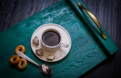 Coffee cup with coffee on a tray. The tray stands on a black wooden background. Next to a cup of coffee sugar with cinnamon, tea spoon and bagels stock images