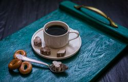 Coffee cup with coffee on a tray. The tray stands on a black wooden background. Next to a cup of coffee sugar with cinnamon, tea spoon and bagels stock photography