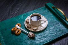Coffee cup with coffee on a tray. The tray stands on a black wooden background. Next to a cup of coffee sugar with cinnamon, tea spoon and bagels royalty free stock photo