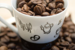 Coffee cup with coffeebeans. Coffee cup and coffeebeans in and arround the cup Royalty Free Stock Photos