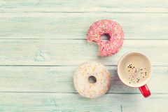Coffee cup and colorful donuts Stock Images
