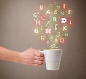 Coffee cup with colorful letters Royalty Free Stock Photos
