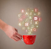 Coffee cup with colorful letters Royalty Free Stock Images