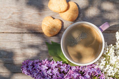 Coffee cup and colorful lilac flowers on garden table Stock Images