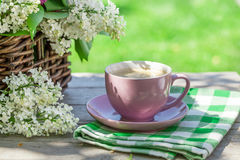 Coffee cup and colorful lilac flowers on table Stock Photos